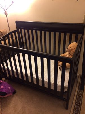Black wooden convertible crib with mattress