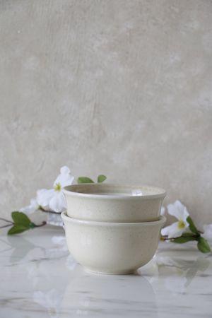 two cream ceramic bowls