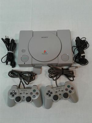 Vintage original PlayStation one with two controllers and cables