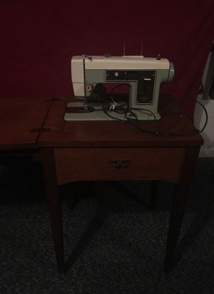Small wooden cabinet with sewing machine inside