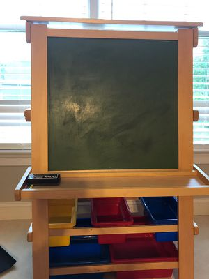 Dry erase board and chalk board easel with storage boxes underneath.
