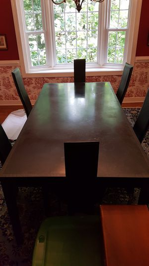 Black slate table with 8 leather chairs.