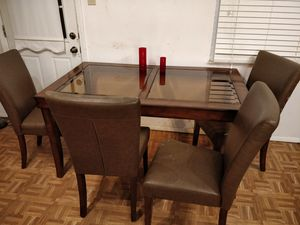 Nice wood and glass top dining table with 4 lather chairs in good condition