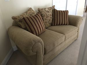beige fabric loveseat with pillows