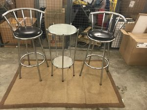Two black metal bar stools and a silver table