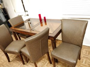 Nice wood and glass top dining table with 4 lather chairs in good condition,